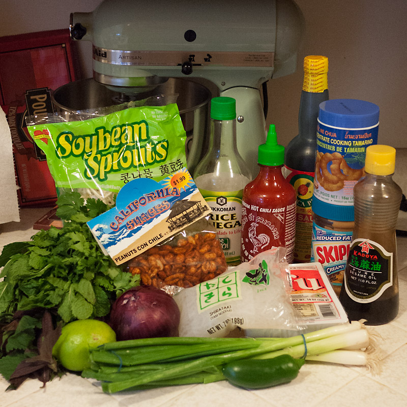 I know it looks like a lot of ingredients (please ignore Martha Bourdain, my mixer, and the one pound chocolate bar in the background), but once you have a majority of these ingredients, cooking anything Asian-inspired will be a breeze. They're kitchen staples! Bean sprouts, rice vinegar, sriracha, soy sauce, tamarind paste, peanut butter, tofu, shirataki oodles, greenion onions, jalapeno, red onion, lime, red perilla, mint, cilantro, and chili peanuts.